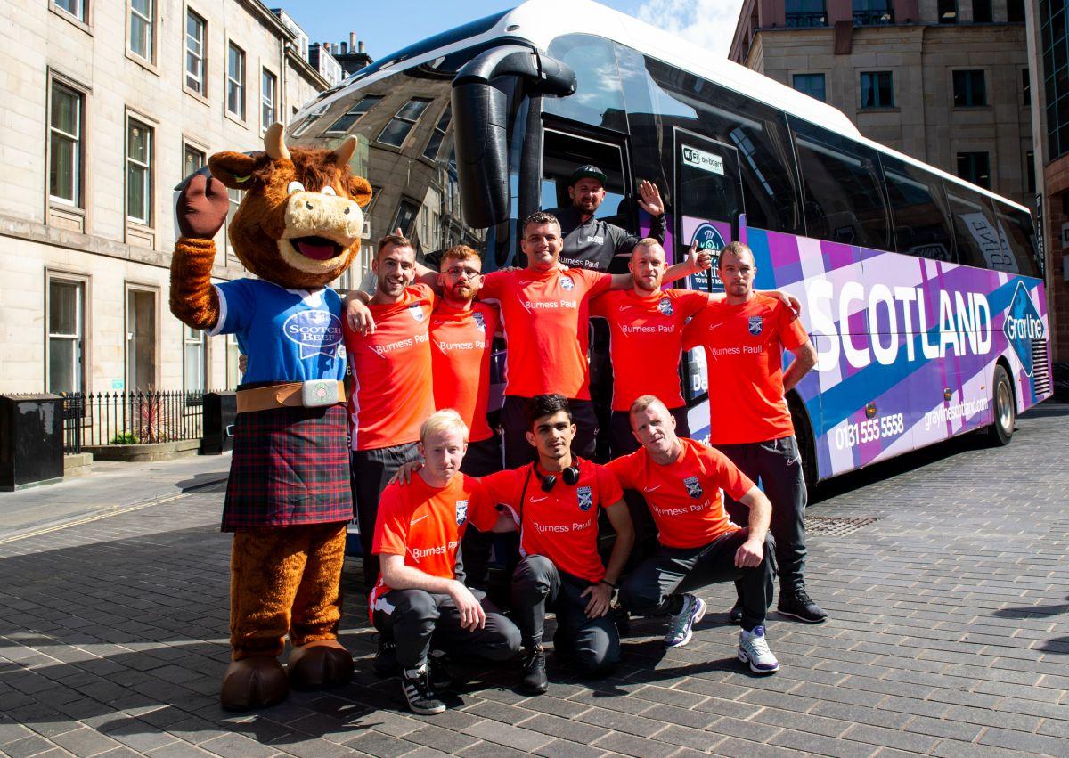 eight men in football strips beside a bus
